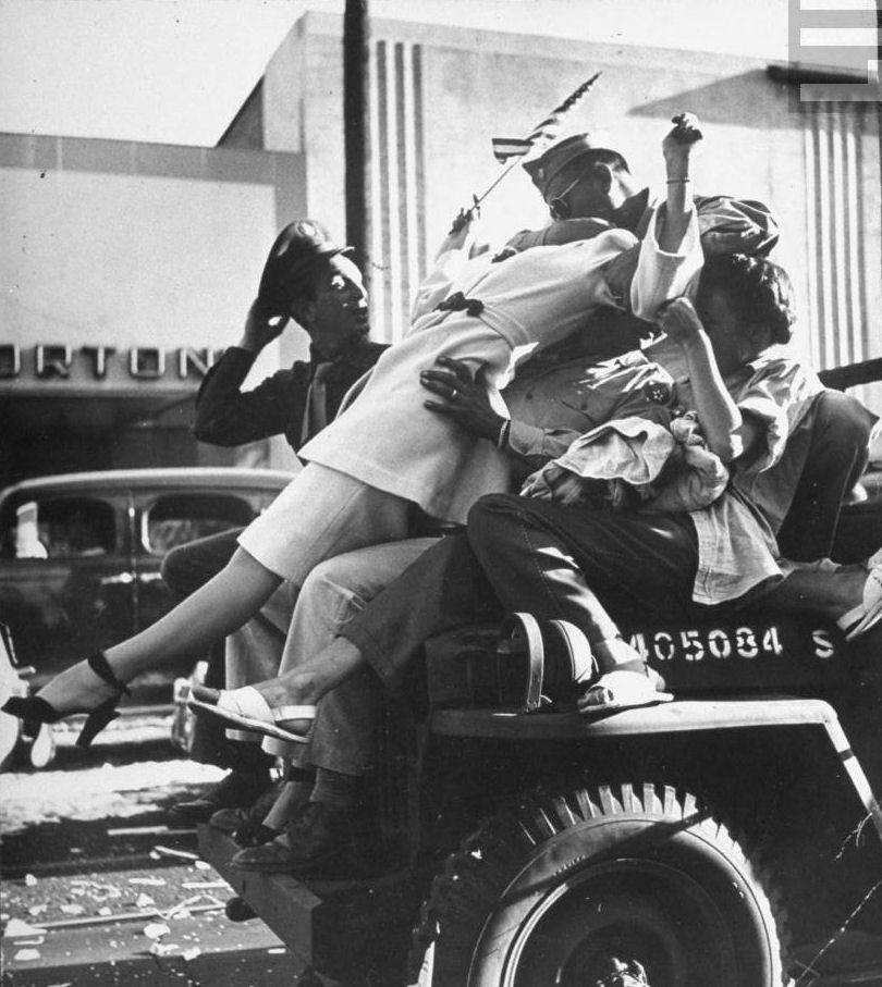 Jubilant soldier kissing, flag-waving woman as they ride on hood of a military jeep during impromptu celebration of the end of WWII.jpg