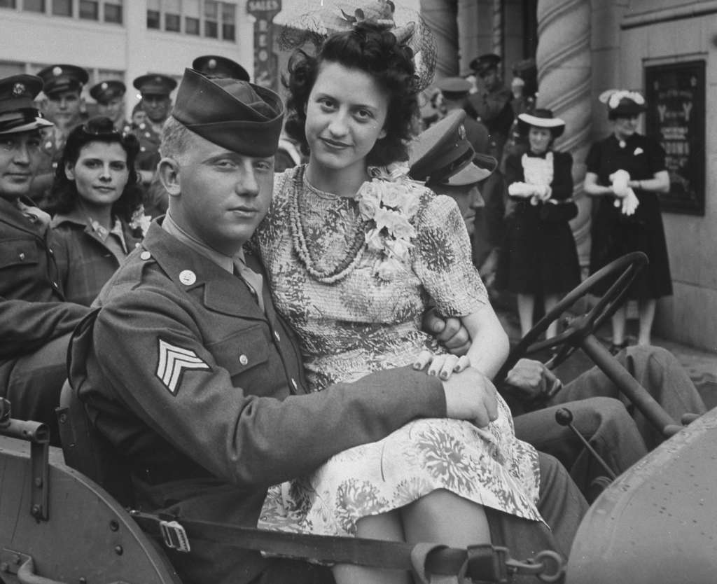 Soldiers and their brides sitting in a jeep_1024x1024.jpg