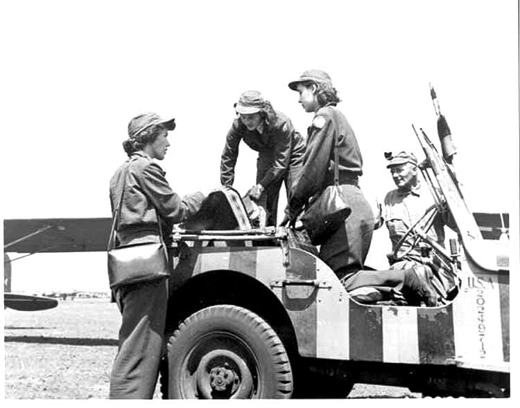 WASP in their santiago blue uniform with the WASP handbag on an airfield.jpg
