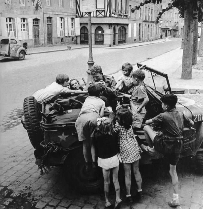 Children climb up to reach the fred feekarts chocolate ration proffered by the jeep driver Dinard france, 1944  Lee Miller.jpg