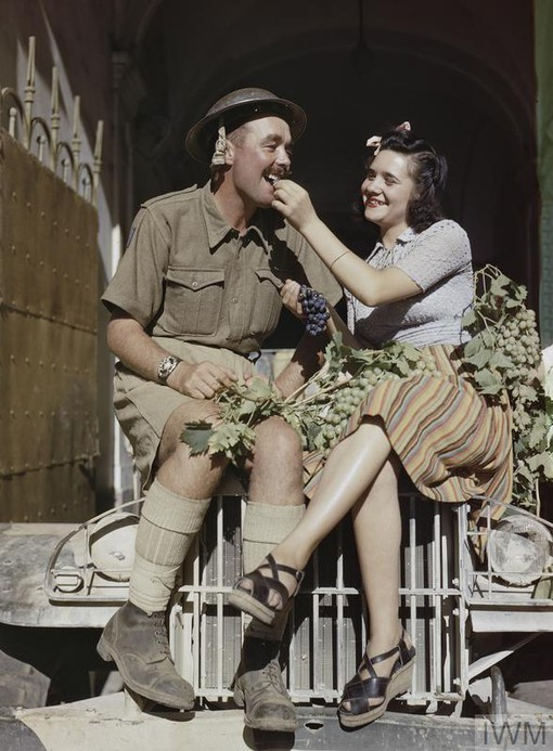 An 8th Army soldier being fed grapes by a pretty Sicilian girl while they ride on the front of a jeep-aug1943.jpg