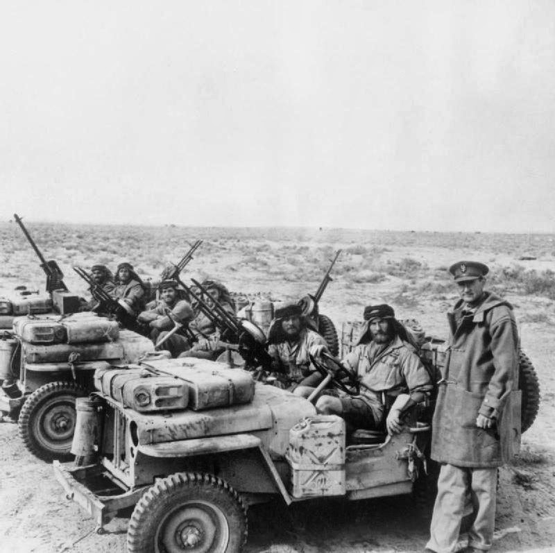 A Special Air Service jeep patrol is greeted by its commander, Colonel David Stirling, on its return from the desert. 18 January 1943.jpg