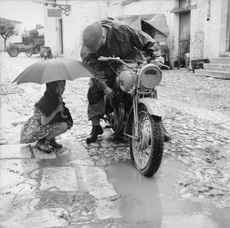 A_little_girl_holding_an_umbrella_watches_a_despatch_rider_attempt_to_clear_the_carbuerettor_of_his_motorcycle_in_torrential_rain,_4_October_1943._NA7526.jpg