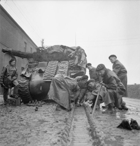 REME troops work to repair the track on a Sherman tank in heavy rain%2C near Geilenkirchen%2C 25 November 1944. %28Small%29.jpg