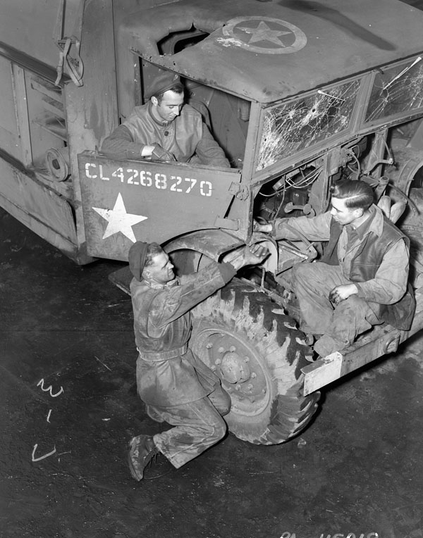 Personnel repairing a bomb-damaged truck of the 1st Canadian Railway Telegraph Company%2C Royal Canadian Engineers %28R.C.E.%29%2C Louvain%2C Belgium%2C 6 January 1945..jpg