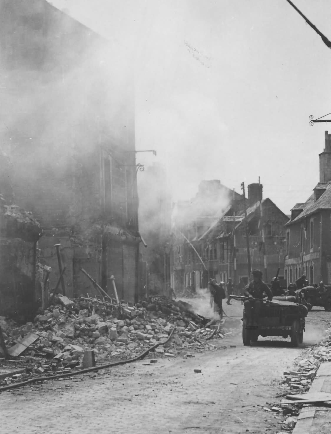 Photo_Fireman_Put_Out_Fire_in_Carentan_Normandy_France_1944.jpg